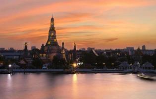 Wat Arun sunset light reflection pool in Bangkok Thailand.
