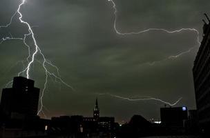 Lightning across a few buildings at night photo
