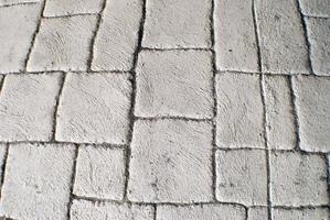 textured background of white pavers under a bridge