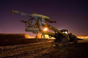 Portrait of a large heavy drilling machine under a dusk sky