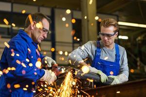 Two workers working with angle grinder photo