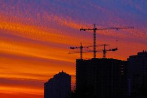 Silhouette of buildings with cranes against sunset sky