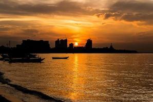 Silhouette of Pattaya beach and city at sunset photo