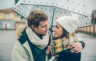 Young couple embracing outdoors under umbrella in a rainy day