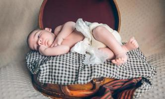 Newborn baby resting lying above of travel suitcase