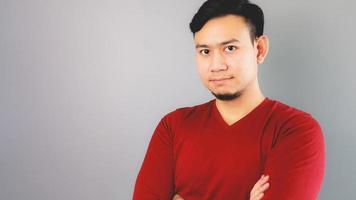 Hombre asiático en camiseta roja está cruzando los brazos.