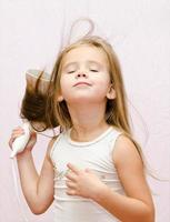 Cute smiling Little girl dries hair