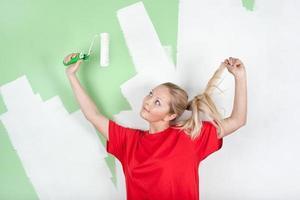 mujer en camiseta roja con rodillo de pintura