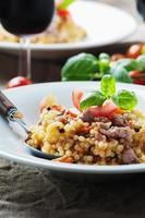 Cooked sardinain pasta fregola with tomato and sausage photo