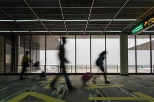 moving blur motion of people walking in airport walkway photo