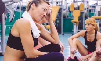 Mujer cansada con una toalla descansando en el gimnasio después del entrenamiento