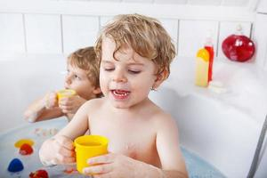 Two little twins boys taking bath photo