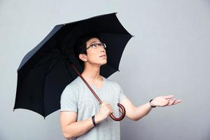 Asian man standing with umbrella photo