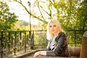 hermosa niña en un banco en el sol foto