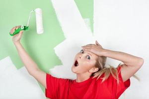 Shocked woman with paint roller in hand photo
