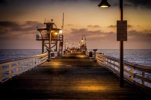 People walking a pier at sunset