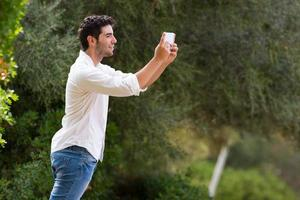 young man searching internet coverage outdoor photo