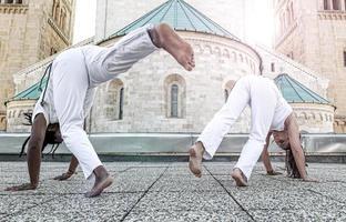 Young pair capoeira partners performing kicks outdoor photo