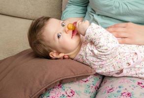 bebê brincando com chupeta deitado sobre as pernas da mãe