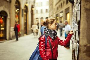 Turista recogiendo postales en siena