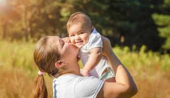 joven madre besando a su bebé foto