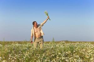 el joven feliz en campo con ramo de camomiles