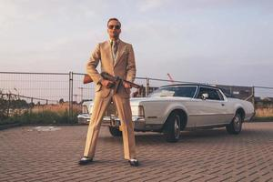 Retro 1970s gangster holding gun standing in front of car.