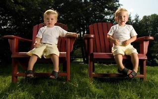 tweelingbroers zittend op rode stoelen