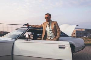 Retro 1970s gangster with pistol leaning against vintage car.