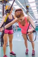 entrenador personal enseñando a mujer en entrenamiento de suspensión