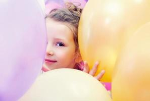 Cute little girl peeking out from behind balloons photo