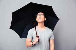 Asian man standing with umbrella and looking up photo