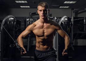 joven atlético bombeo de músculos en crossover foto