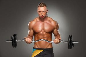 Portrait of super fit muscular young man working out in