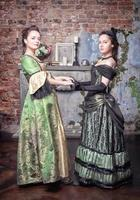 Two beautiful women in medieval dresses photo