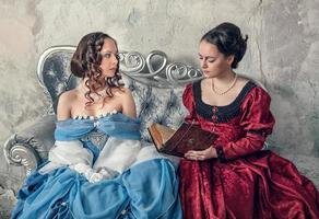 Two beautiful women in medieval dresses on sofa reading book