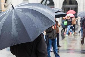 personas con paraguas de lluvia en la ciudad
