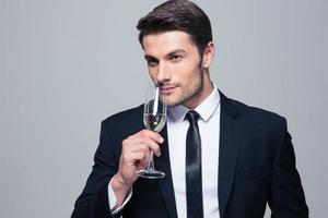 Businessman holding glass of champagne photo