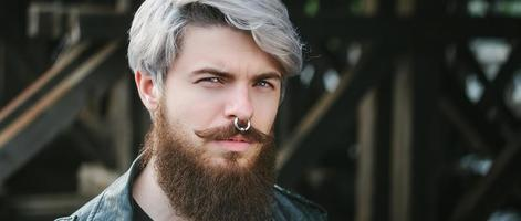 Bearded hipster with nose ring in leather jacket photo