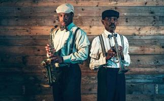 Two african american jazz musicians with trumpet and saxophone. photo