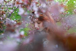 portrait of beautiful woman near the cherry blossom branch.