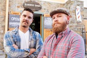 Retrato de dos barberos hipster de pie fuera de la tienda foto