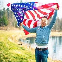 Handsome man outdoors with american flag photo