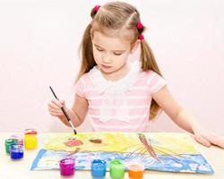 Cute little girl drawing with paint and paintbrush photo