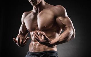 chico musculoso sobre fondo negro foto