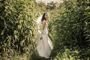 gelukkige mooie bruid die zich in gras en smilling bevindt.