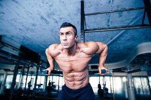 Young muscular man workout on bars