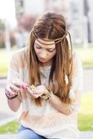 Portrait of hippie young woman playing with daisies. photo