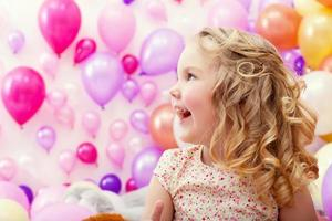 Adorable cheerful girl on balloons background photo