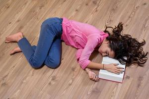 Young girl  student sleeping at the parquet  with book. photo